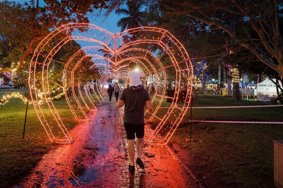 People walk through a heart-shaped tunnel of red Christmas lights.