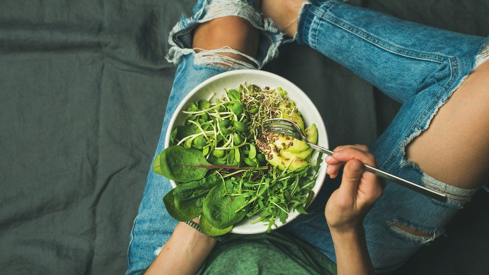 Young woman sitting holding a bowl full of spinach, rocket and avocado.