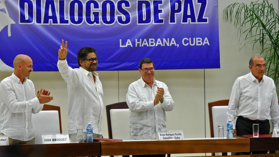 Commander Ivan Marquez flashes the V sign after the signing of the agreement at the conclusion of the peace talks at the Convention Palace in Havana, on August 24, 2016, next to Norway's guarantor for the peace talks, Dag Nylander Cuban Foreign Minister Bruno Rodriguez and Colombian government head of delegation Humberto de la Calle (R).