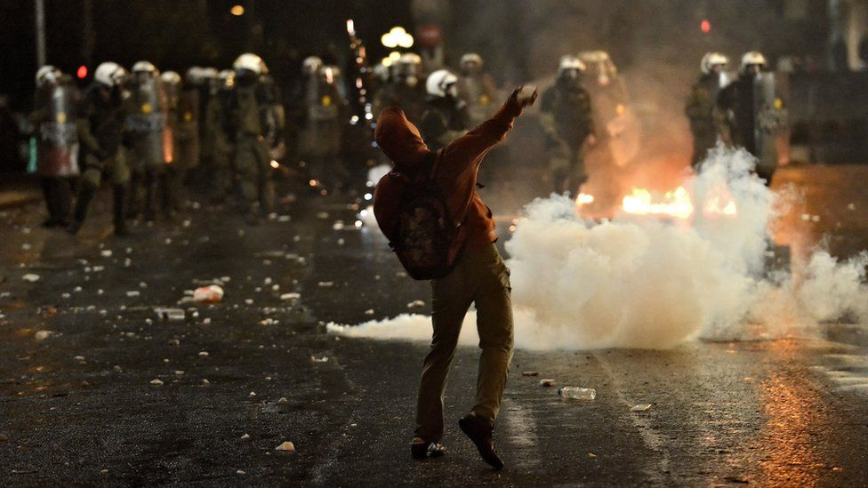 A hooded protester throws a rock at a line of riot police in Athens. A canister of tear gas is deployed on the street.