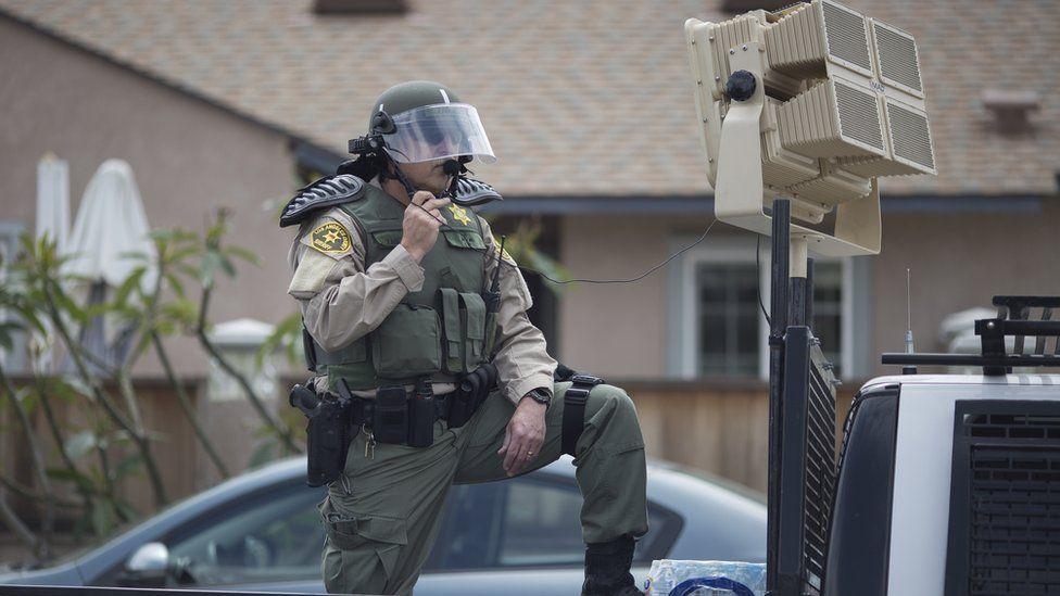 Man in riot police gear behind speaker device