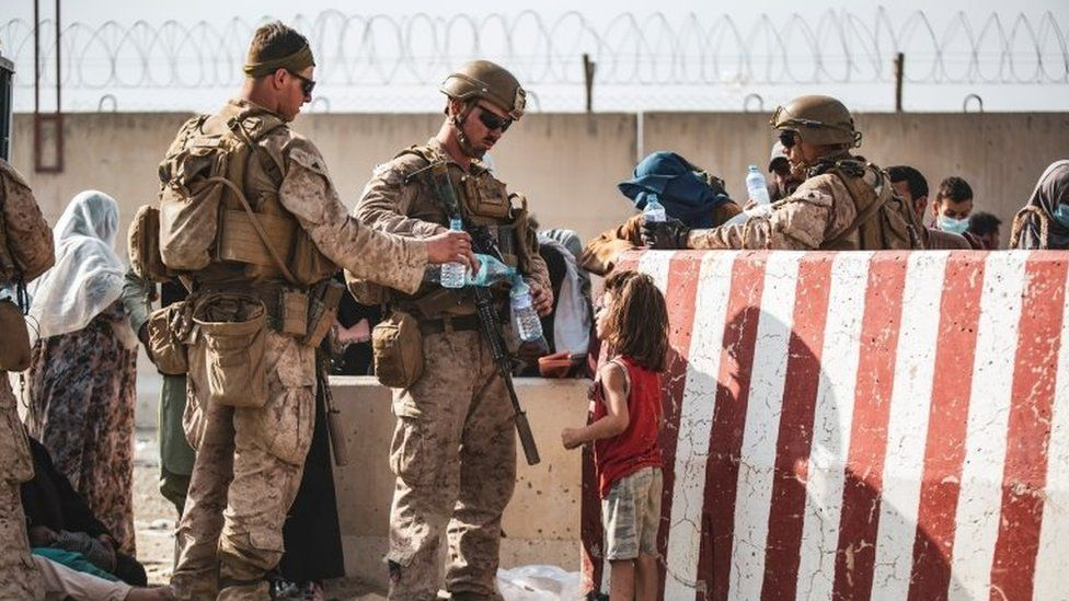 U.S. Marine hand out water during an evacuation at Hamid Karzai International Airport
