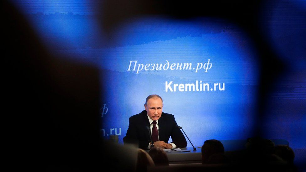 A picture of Vladimir Putin at a news conference