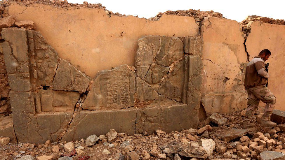 A soldier walks past a smashed artefact at Nimrud
