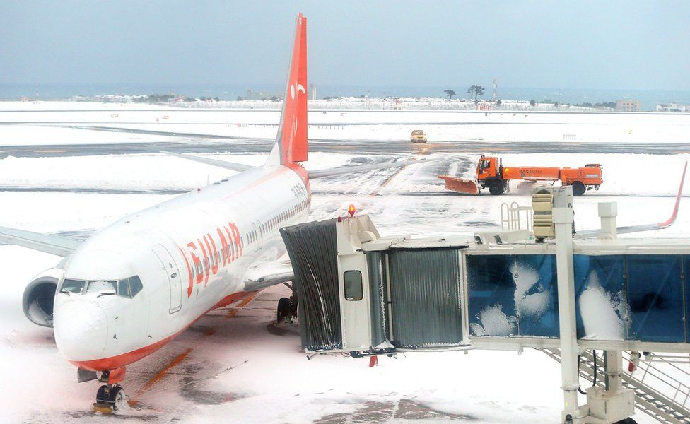 A general view shows a Jeju airlines Boeing 737 aircraft parked amid snow coverage at Jeju airport on 25 January 2015