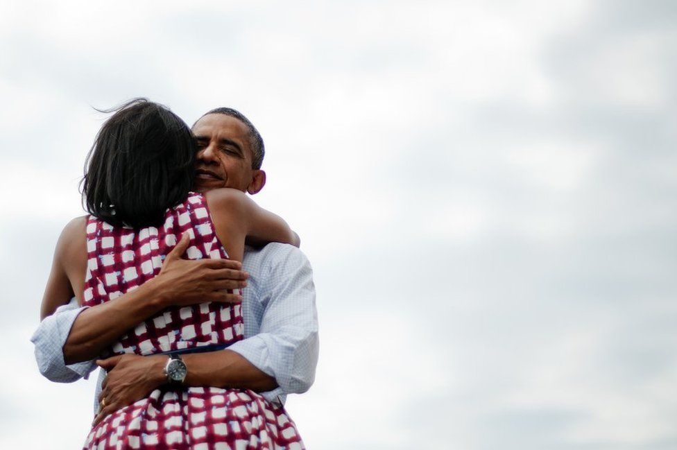 Then US President Barack Obama hugs his wife Michelle Obama during his campaign tour on 15 August 2012