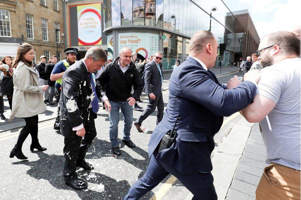 Brexit Party leader Nigel Farage reels from having a milkshake thrown at him