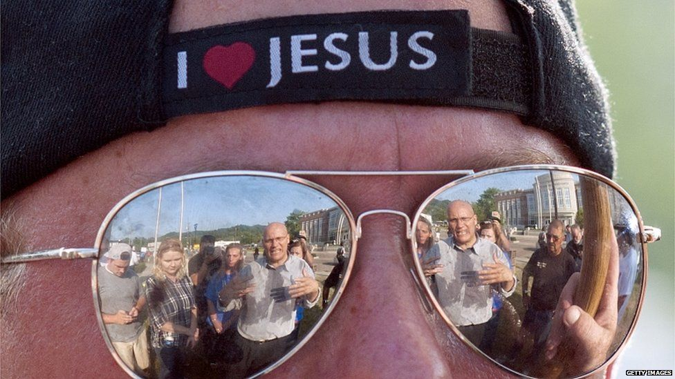 The reflection of a man speaking with protestors in opposition of same sex marriage is reflected in the sun glasses of Mike Reynolds, a opposer of same sex marriage, during a protest in front of the Rowan County Courthouse on 3 September 2015 in Morehead, Kentucky.