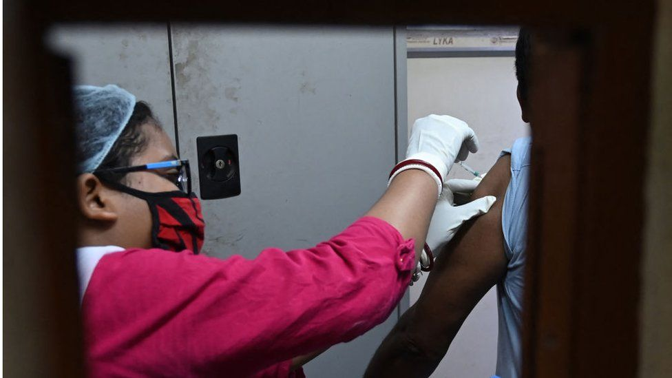A health worker inoculates a man with a dose of Covaxin Covid-19 coronavirus vaccine