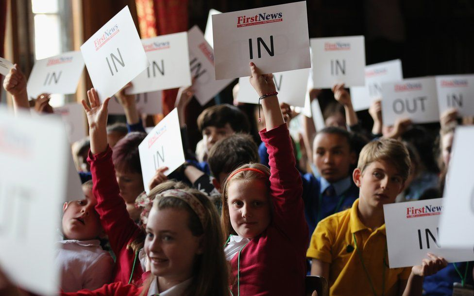 "Children of school age holding up ""in"" and the occasional ""out"" signs"