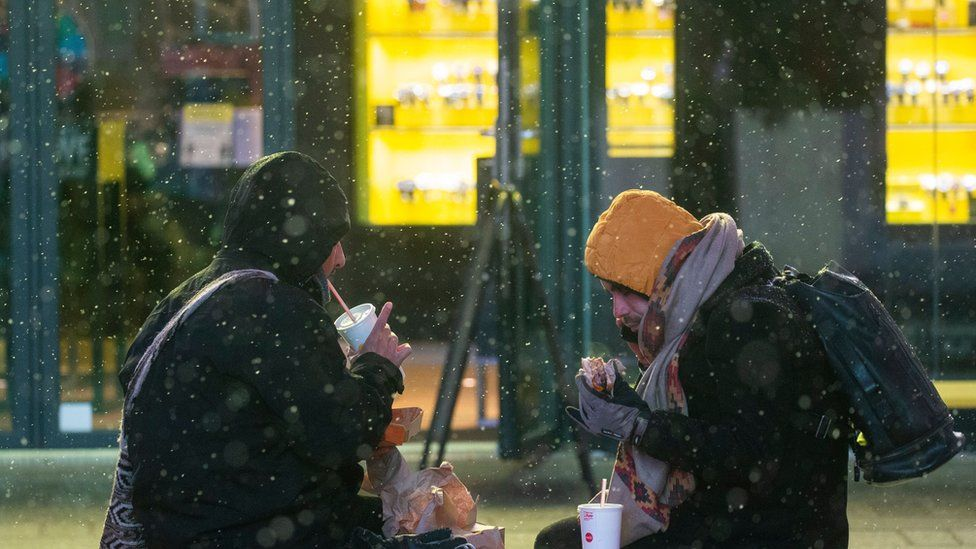 People eat as snow falls during a winter storm in Times Square New York