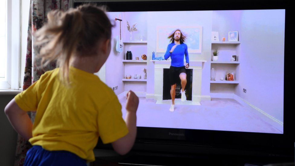 Child follows Joe Wicks' PE session