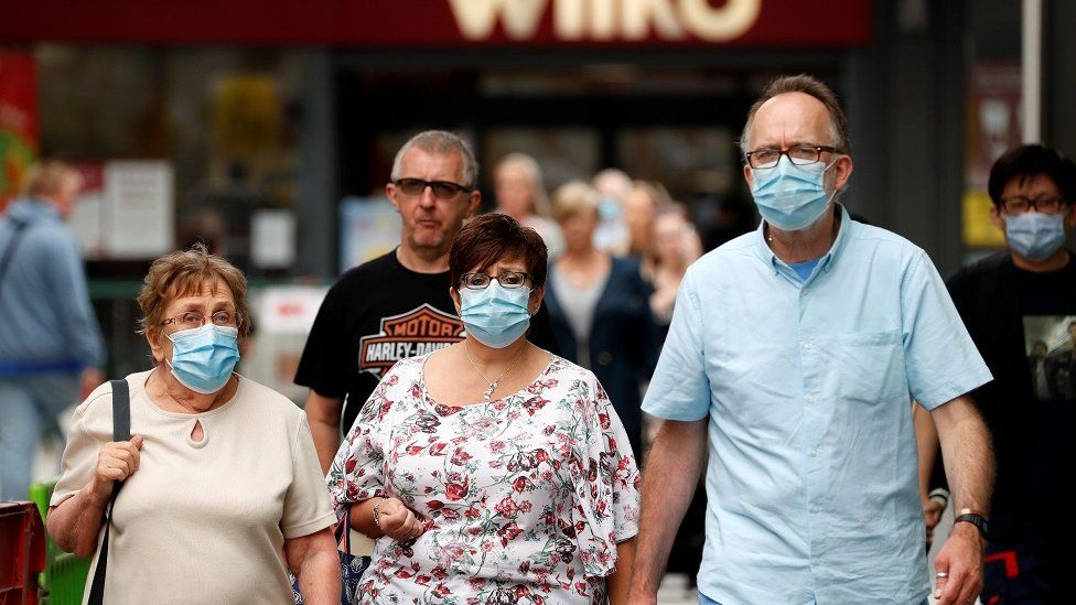 Shoppers, some wearing a face mask or covering due to the COVID-19 pandemic, walk past shops in Basingstoke, south west of London, on July 23, 2020, as consumers return to the shops following the continued lifting of novel coronavirus lockdown restrictions. - Facemasks will become compulsory in shops and supermarkets in England from Friday, after weeks of wrangling from ministers about their effectiveness.