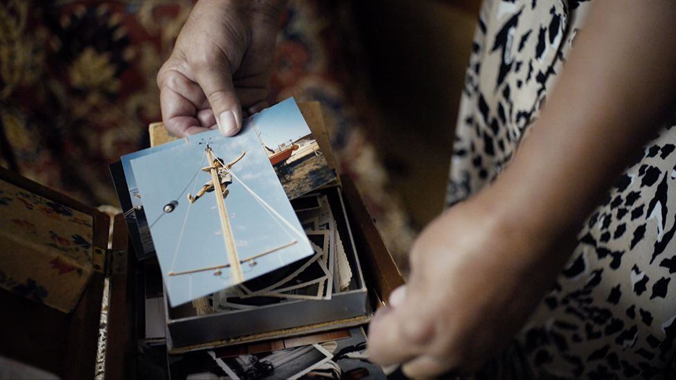Carlotta holds a photograph of her climbing the mast of her sailing boat