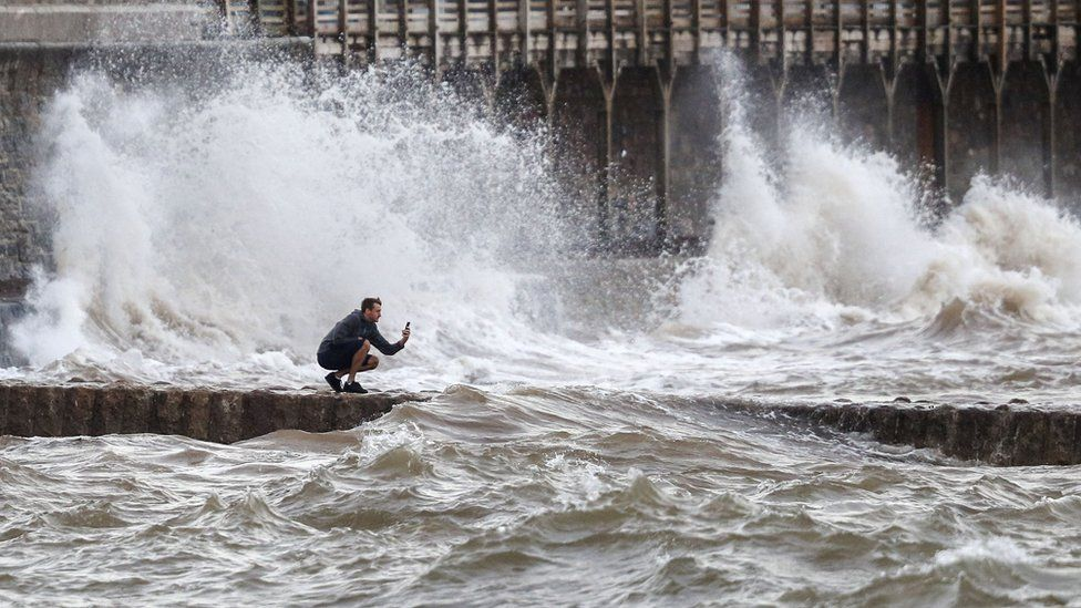 A man takes a photograph of the waves in Dawlish, Devon as gusts of up to 70mph could hit coastal areas as Storm Ellen moves on