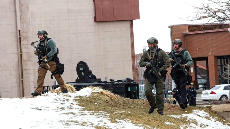 Law enforcement officers sweep the area outside of a King Soopers grocery store, which was the site of a shooting in Boulder, Colorado