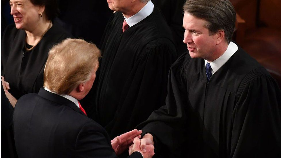 US President Donald Trump shakes hands with US Supreme Court Justice Brett Kavanaugh before delivering the State of the Union address