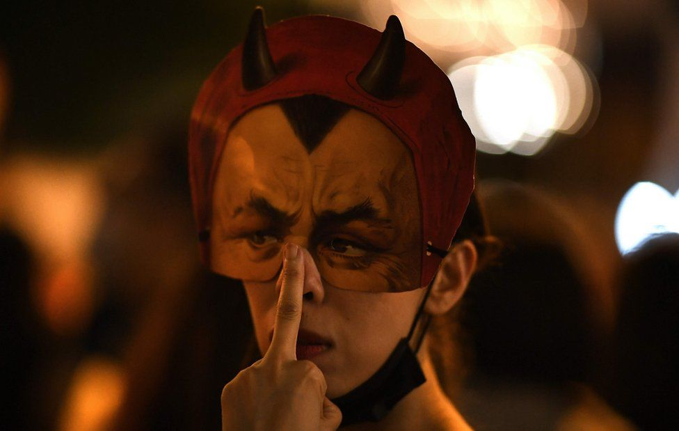 A protester wearing a facemask gestures while people gather in the Admiralty area of Hong Kong