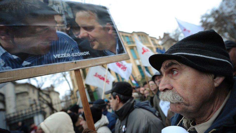 A participant at a 2103 rally holds a banner with a photo of Hungarian Prime Minister Viktor Orban (R) and senior Fidesz party member Zsolt Bayer (L)