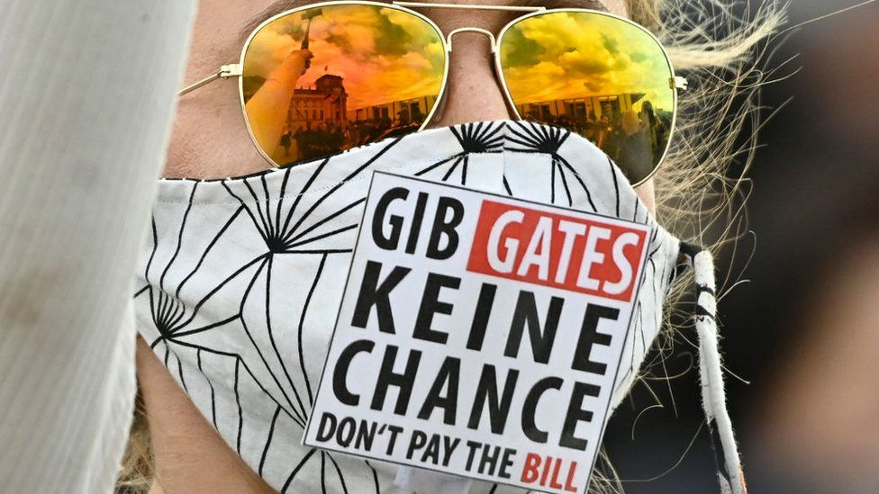"A protester wears a mask which says in German and English: ""GIB GATES KEINE CHANCE DON'T PAY THE BILL"""