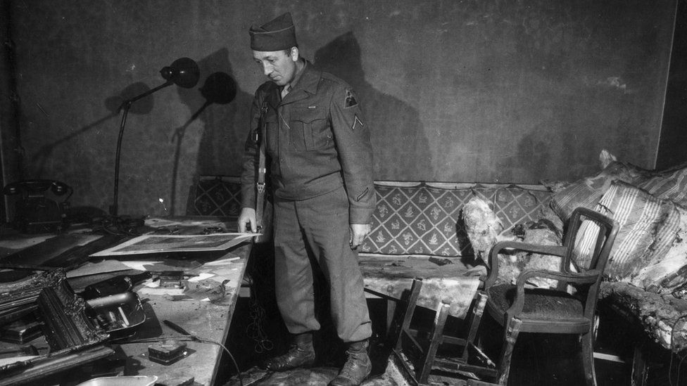 A Soviet soldier in the room where Hitler and Eva Braun were believed to have committed suicide