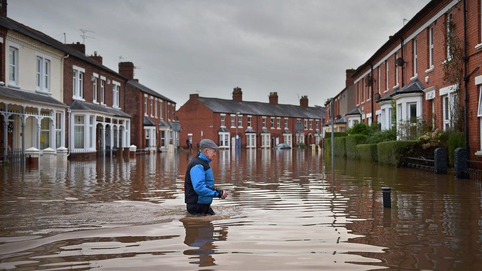 A Carlisle resident makes his way through the floodwater