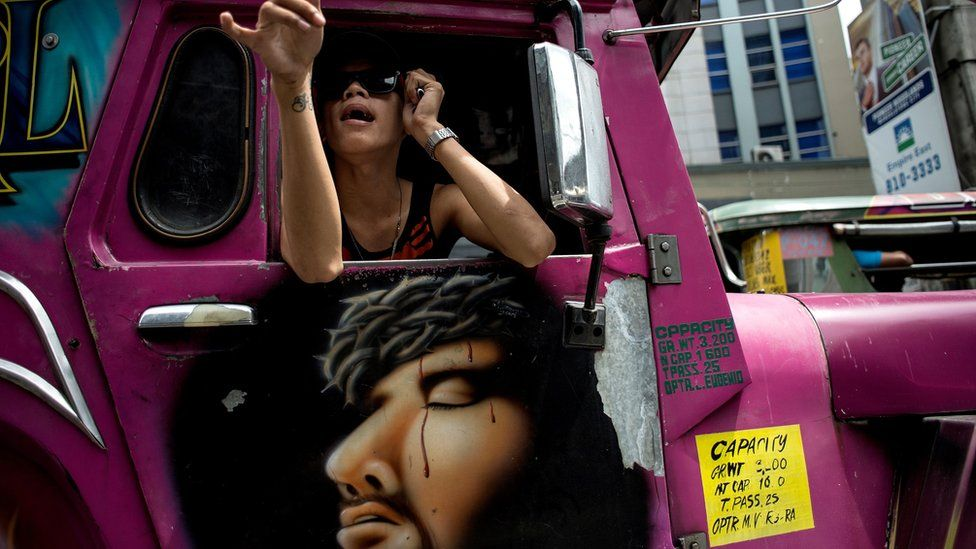 A jeepney driver's assistant calls for passengers at a busy street in Manila