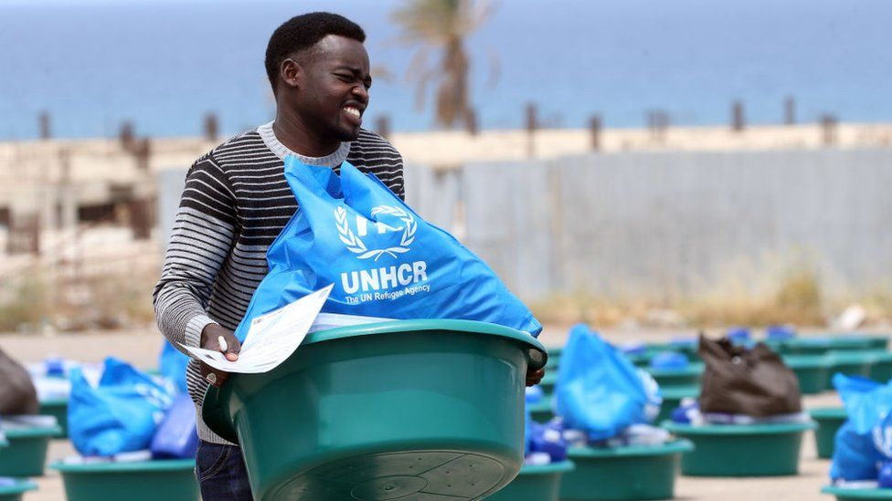 A man caries a bowl with aid items at a United Nations' High Commissioner for Refugees (UNHCR) camp for displaced Libyans and asylum seekers, on May 12, 2020 in the Libyan capital Tripoli during the Muslim holy month of Ramadan.
