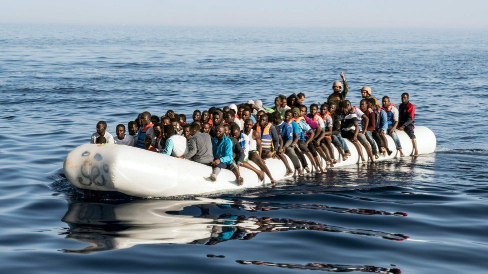 Migrant crisis: Libyan coast guardsmen at sea in an overcrowded dingy with illegal immigrants that were rescued, June 2017