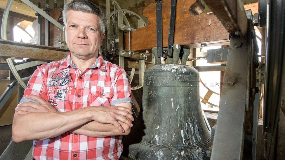 Now former mayor Roland Becker stands next to the church bell embossed with a swastika and the text: 'Everything for the Fatherland Adolf Hitler' in the Jakobskirche village church on June 13, 2017 in Herxheim, Germany.