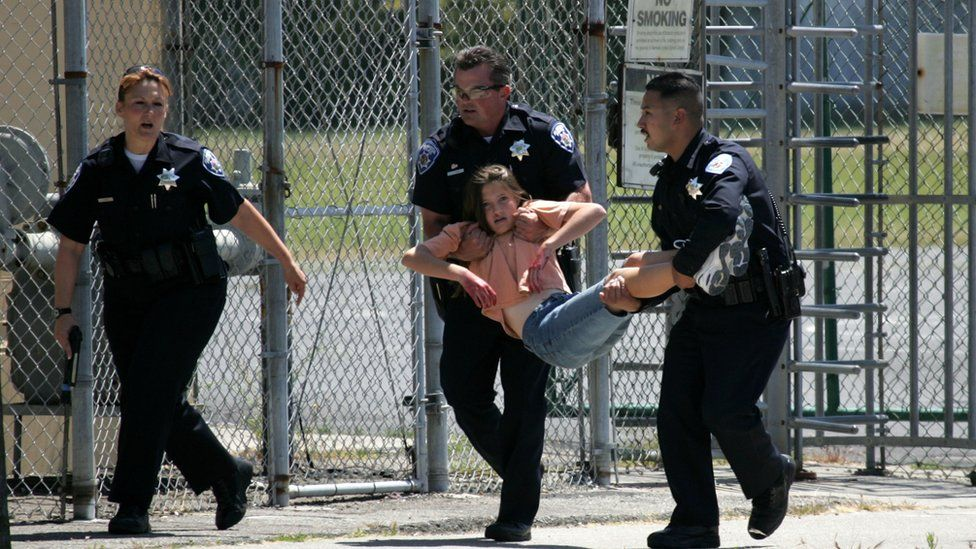 A school student being carried by two police officers during an active-shooter drill