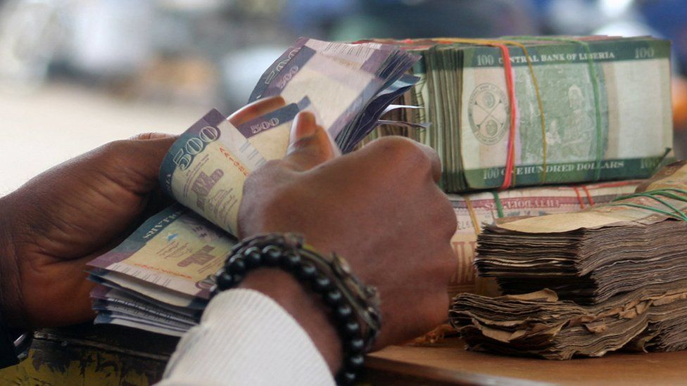 Hands counting money in Liberia
