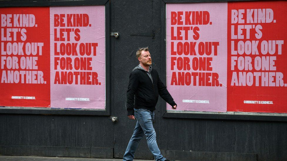 Man in front of 'Be Kind' posters