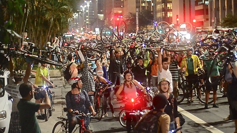 Cyclists cheer during a protest in Sao Paulo