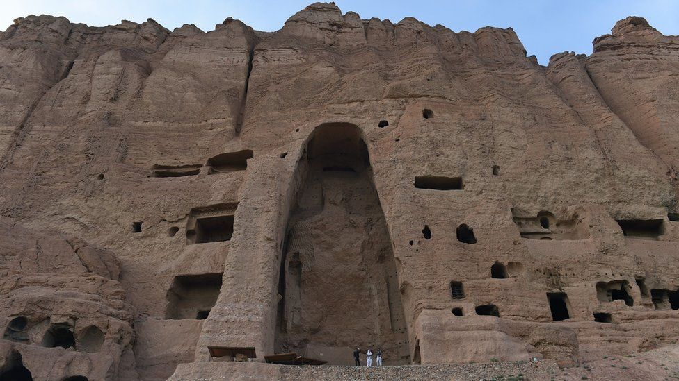 This file photograph taken on June 19, 2015, shows visitors as they walk in front of the empty site of two Buddha statues, which were destroyed by the Taliban, in Bamiyan
