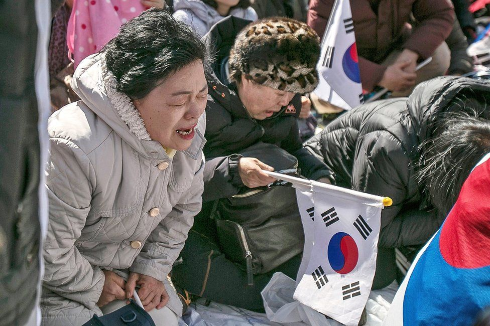 Supporters of President Park Geun-hye react emotionally as the Constitutional Court had ruled the impeachment near the court on 10 March 2017 in Seoul, South Korea