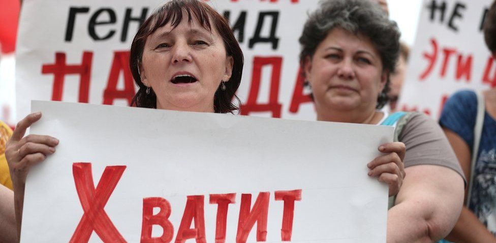 """A Russian protester in Ivanov on 1 July holds a banner saying """"enough"""""""