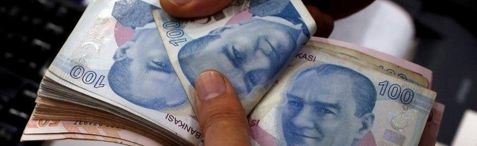 A man counts Turkish lira banknotes