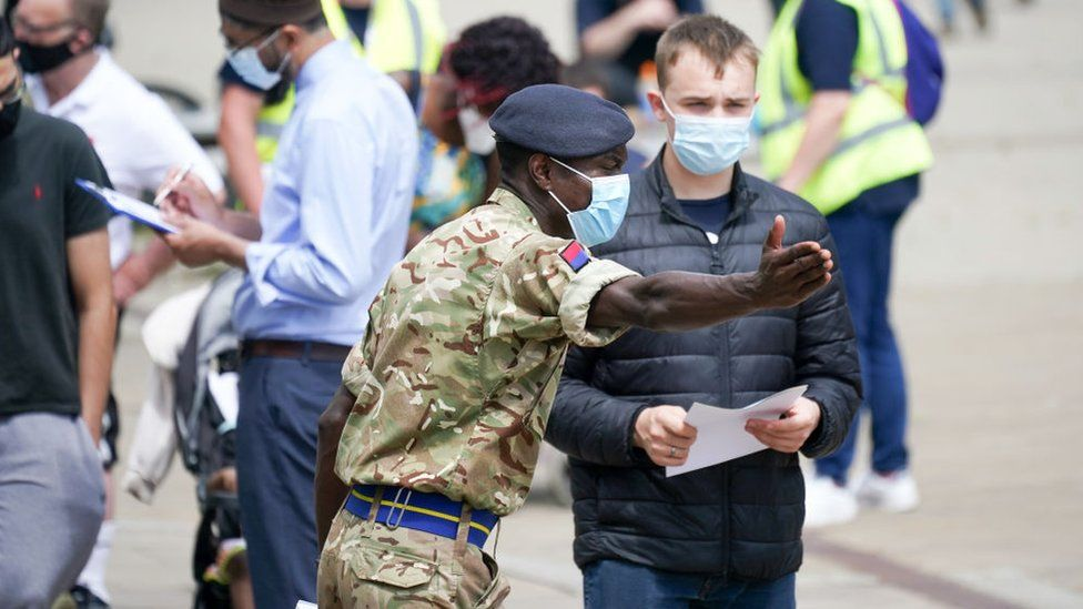 Soldiers guide members of the public to a vaccinate centre in Bolton