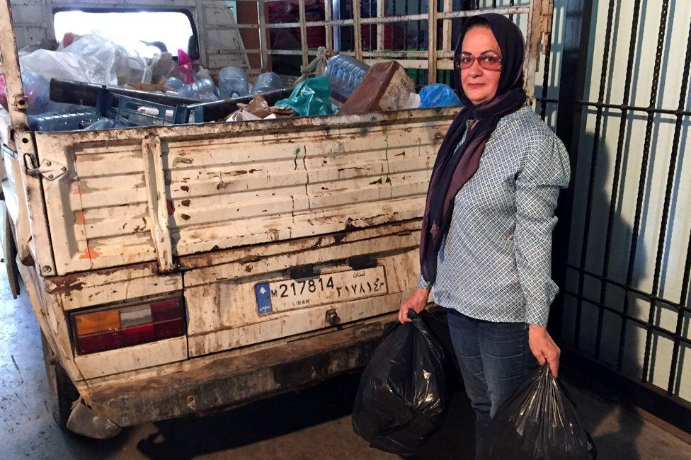 Khadija Farhat holding rubbish bags, standing next to a lorry