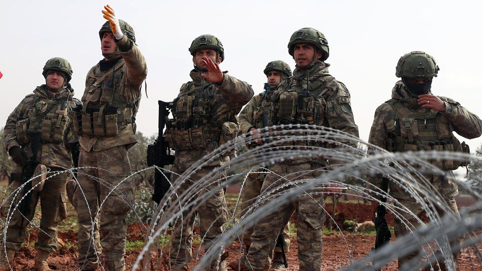 Turkish soldiers stand behind barbed wire at an observation post in Binnish, Idlib province, Syria (14 February 2020)