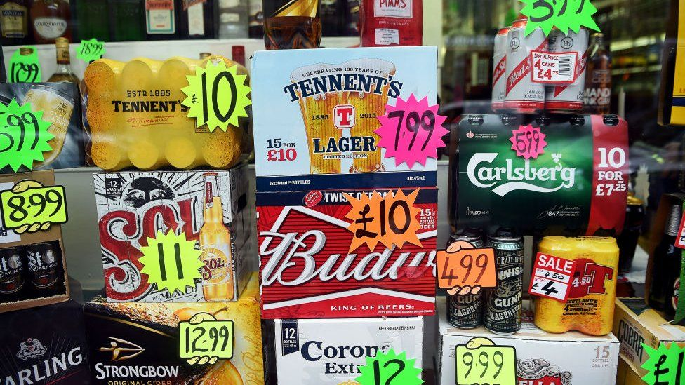Bottles and cans of liquor are displayed with price tags in a shop window in Glasgow
