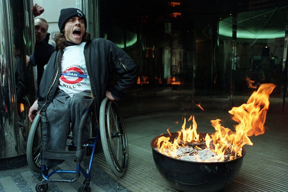 A member of DAN sits beside burning consultation documents, outside the Department of Transport and the Environment in Westminster, central London