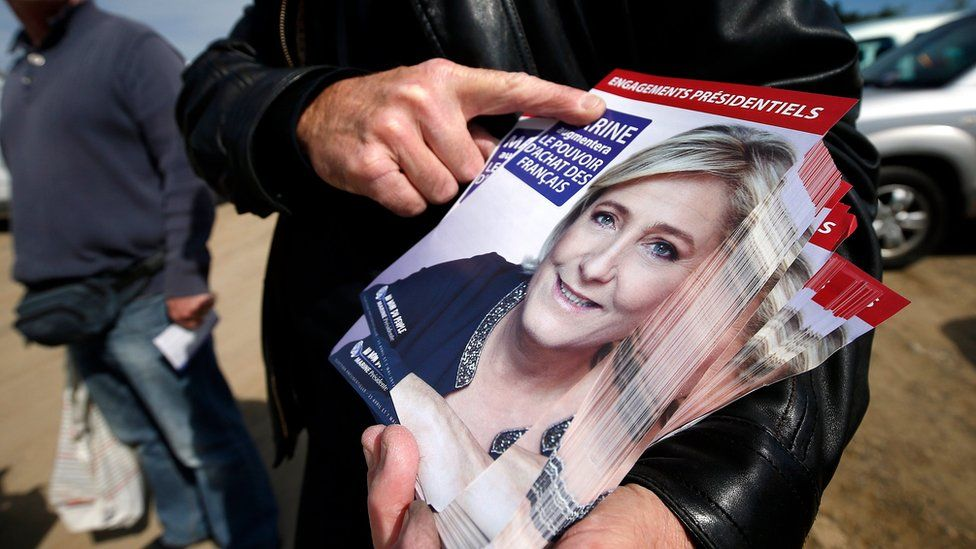 A supporter of Marine Le Pen distributes flyers of French presidential election candidate for far-right Front National (FN) party, Marine Le Pen in Valbonne, southern France, 30 April 2017.