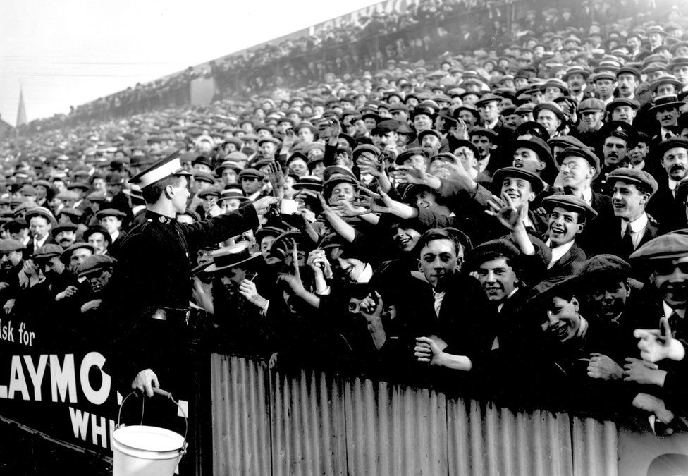 27th September 1913: An ambulance worker handing out water at a crowded football match between Tottenham Hotspur and Manchester City at White Hart Lane in London.