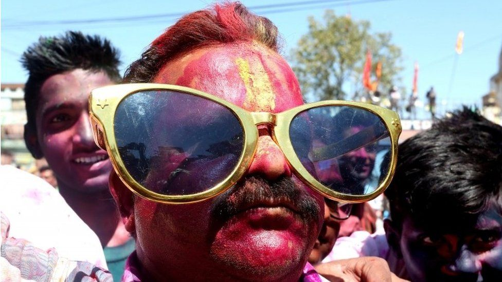 A Indian man with his face covered with paint pose for a picture during the Holi festival in Bhopal, India