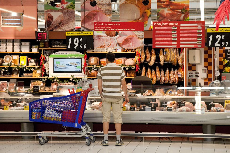 Man at meat counter, supermarket in France