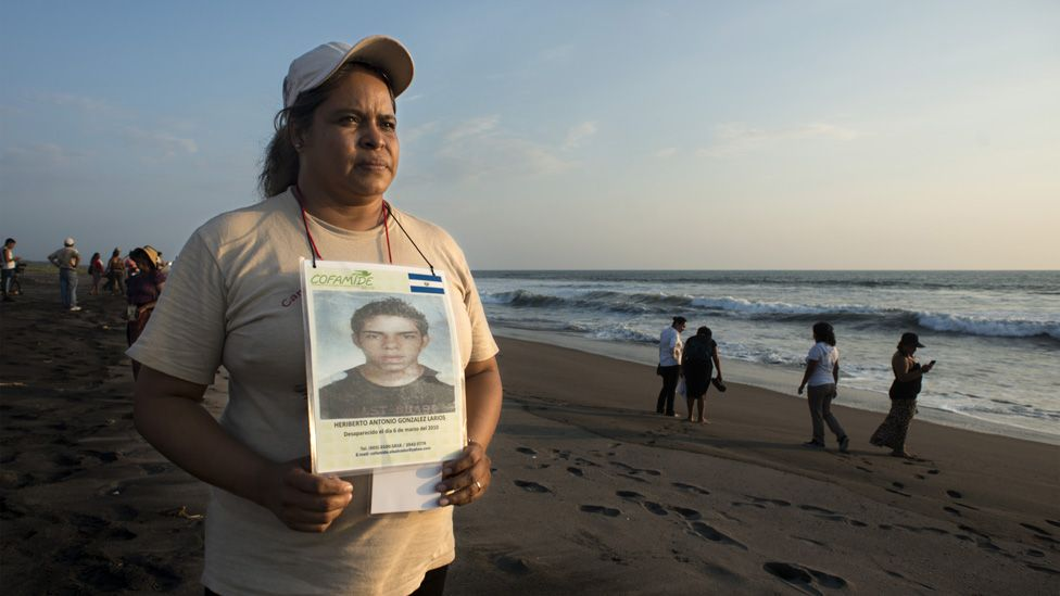 María Elena Larios holds up a picture of her son