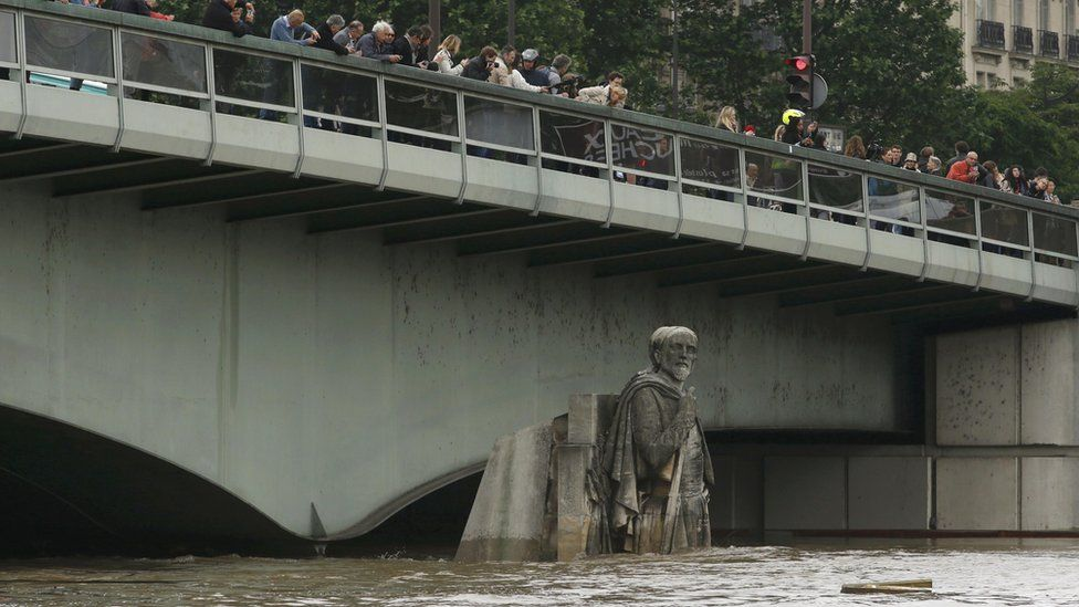 Crowd on the Alma bridge in 2016 - the water only reaches the Zouave's upper legs