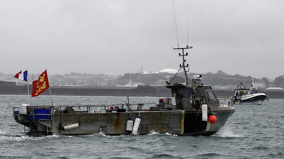 A French fishing boat, one of several, takes part in a protest in front of the port of Saint Helier off the British island of Jersey to draw attention to what they see as unfair restrictions on their ability to fish in UK waters after Brexit, on May 6, 2021